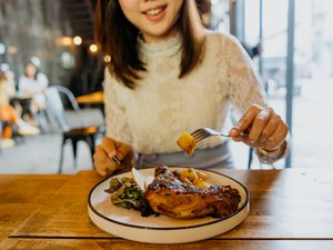 Asian woman enjoying a whole chicken leg meal in a cafe