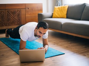 Man uses laptop while performing a forearm plank