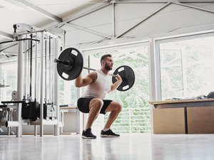 Young man doing barbell back squats