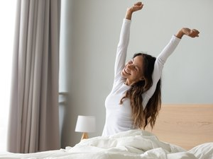 A woman in bed waking up refreshed after she got better sleep