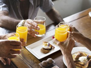 people clinking orange juice glass together at breakfast at hotel
