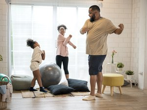 father and his two daughters exercising at home
