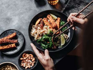 Woman eating Asian dish with chopsticks