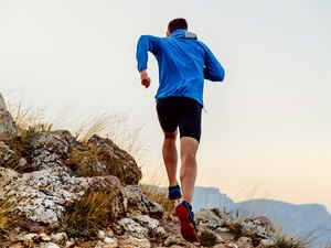 back runner man athlete running uphill trail over stones
