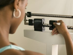 Woman Weighing Herself to determine her pounds of body fat