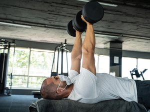 fit man bench pressing dumbbells at the gym during covid-19 pandemic