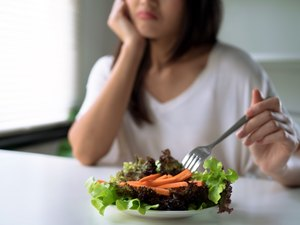 Unhappy women is on dieting time, girl do not want to eat vegetables.