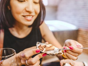 Woman eating a zinc-rich oyster, close-up at a restaurant