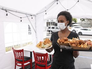Young Waitress Serving Food to Customers in Outdoor Tent Wearing a Mask