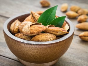 Almond with leaves in wooden bowl