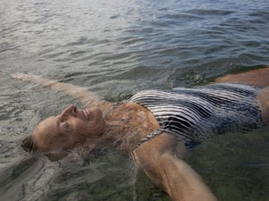 Senior woman floating in pool, arms outstretched, smiling, close-up