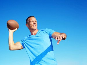 Confident mature man throwing American football against clear blue sky