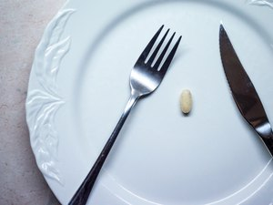 Single Pill/Tablet on a White Dinner Plate Overhead View