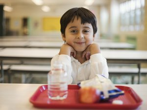 Boy with lunch sitting in school cafeteria