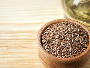 Flax seeds in  wooden bowl , linseed oil on  wooden background