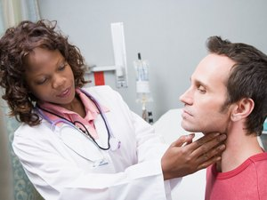 Doctor examining glands of throat of patient
