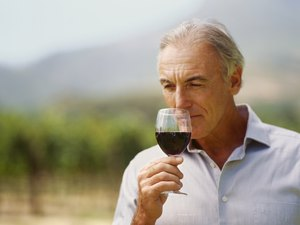 close-up of a mature man sniffing a glass of red wine