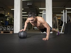 Fit and attractive athlete is performing a one-handed push-up on a medicine ball at the gym.