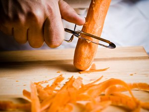 Close-up of cook peeling raw carrot