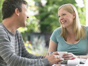 Couple sitting at table holding mugs, looking at each other, laughing