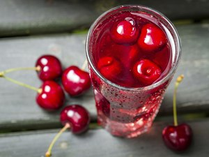 Closeup of fresh juice with sweet cherries and ice