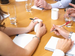 Business colleagues with drinks and notepads on table in meeting