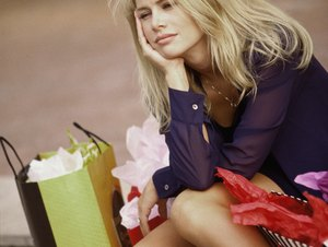 Young woman sitting on the pavement with shopping bags