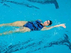 Woman swimming backstroke in pool