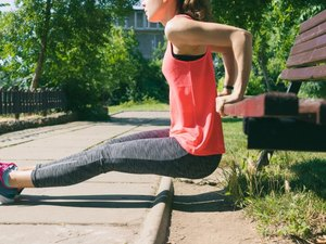 Woman in sportswear doing exercise on triceps on a park bench