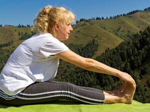 Young woman practices yoga and doing forward bend
