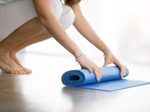 Close up shot of female hands unrolling yoga mat in a modern apartment, preparing for practice in class or at home. Yoga studio etiquette. Healthy lifestyle concept