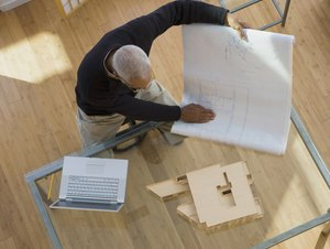 African architect looking at building model and blueprints