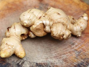 fresh ginger root on wooden chopping block.