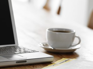 close up of a laptop on a kitchen table with a cup of coffee
