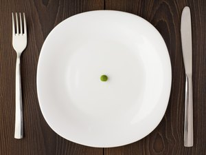 One pea on a white plate