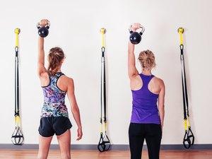Women doing shoulder press with kettlebells