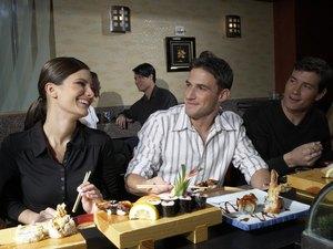 People in sushi bar, man and woman flirting