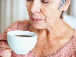 Senior lady blowing her hot coffee