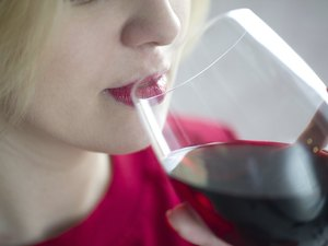 Woman drinking red wine with red lips - close portrait