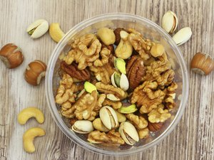 Selection of mixed nuts in plastic box on wooden surface