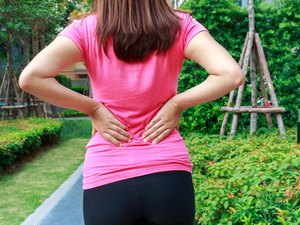 Female athlete lower back painful injury. Sporty woman backache and injury.