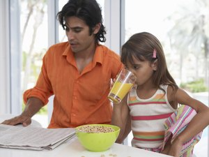 Father reading newspaper sitting with daughter (7-9) having breakfast
