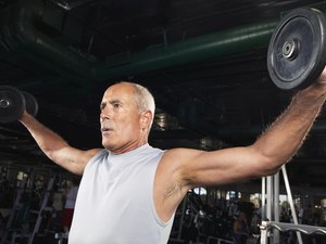 Mature man weight training in gym, low angle view