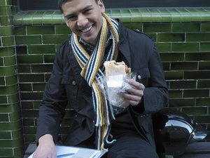 Young man sitting outside holding lunch,smiling, portrait