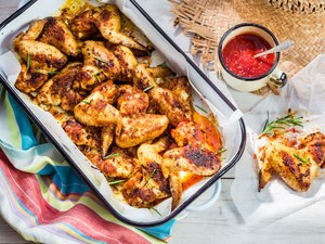 Spicy chicken wings with herbs and sauce in rustic kitchen