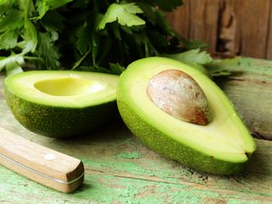 ripe avocado cut in half on a wooden table
