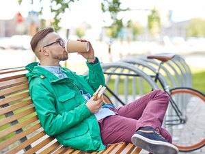happy young hipster man with coffee and sandwich