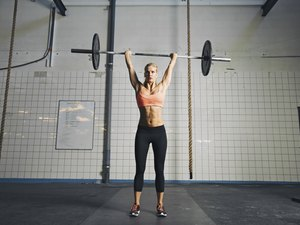 Young strong woman doing weight lifting
