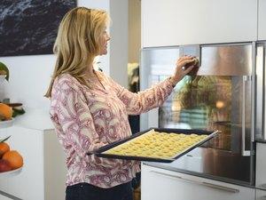 Mature woman baking cookies in kitchen