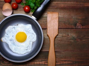 Pan of fried egg, with cherry-tomatoes and parsley